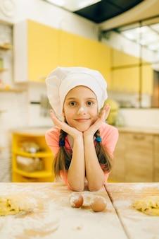 Menina cozinheira de boné e avental na cozinha