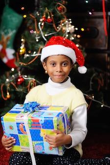 Menina, criança, americano africano, em, chapéu vermelho, papai noel, com, presente natal
