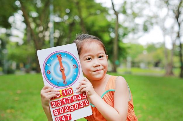 Menina criança aparecendo 6 horas relógio de brinquedo de papel no jardim