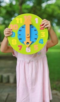 Menina criança aparecendo 6 horas relógio de brinquedo redondo no jardim