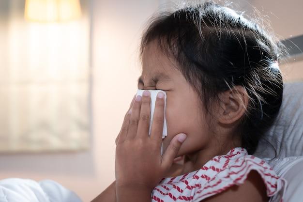 Menina criança asiática adoece, tosse e espirros.