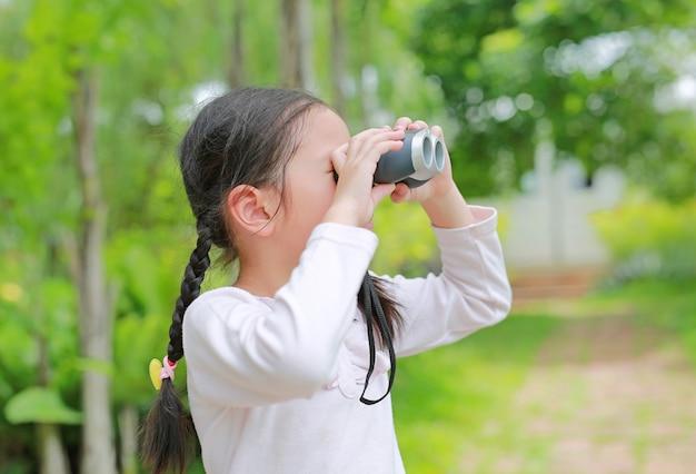Menina criança asiática com binóculos em campos da natureza