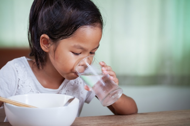 Menina criança asiática comendo macarrão instantâneo delicioso e bebendo água