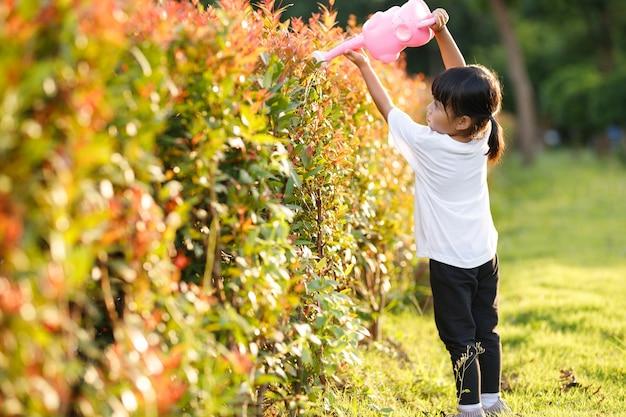 Menina criança asiática derramando água nas árvores. criança ajuda a cuidar das plantas com um regador no jardim.