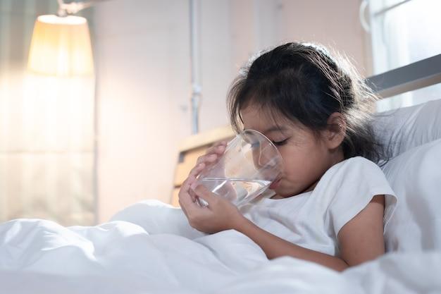 Menina criança asiática doente é beber água de um copo depois de comer remédio no quarto.