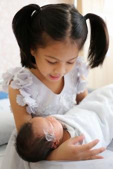 Menina criança asiática está carregando sua irmã no colo.
