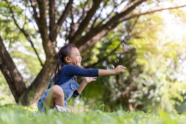 Menina criança asiática feliz soprando bolhas de sabão lá fora no parque verde.