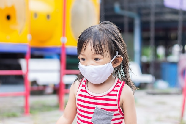 Menina criança asiática feliz sorrindo e usando máscara de tecido. ela está brincando no parquinho.