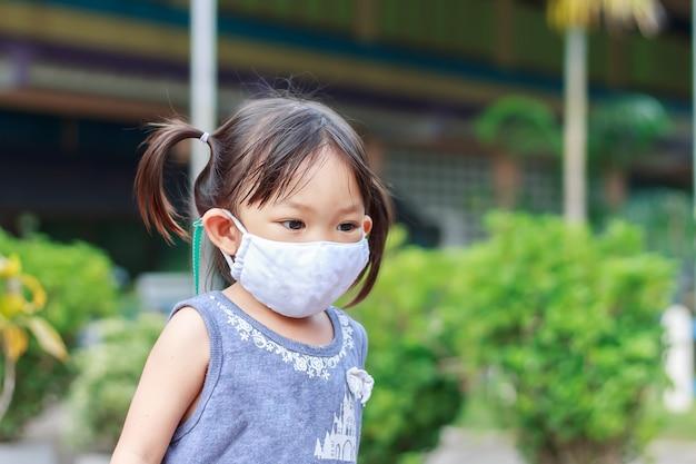 Menina criança asiática feliz sorrindo e usando máscara de tecido.
