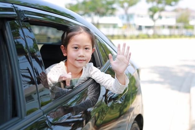 Menina criança asiática no carro, sorrindo e olhando a câmera sentada no banco do carro acenando adeus.