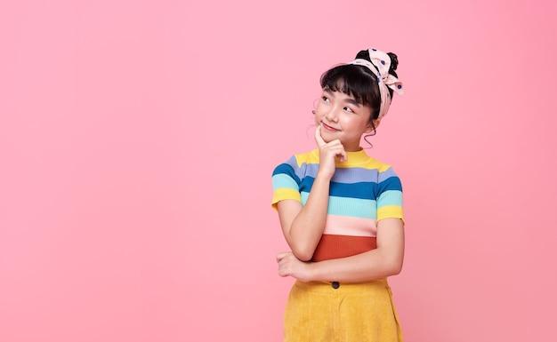 Menina criança asiática pensando em algo isolado na parede rosa.