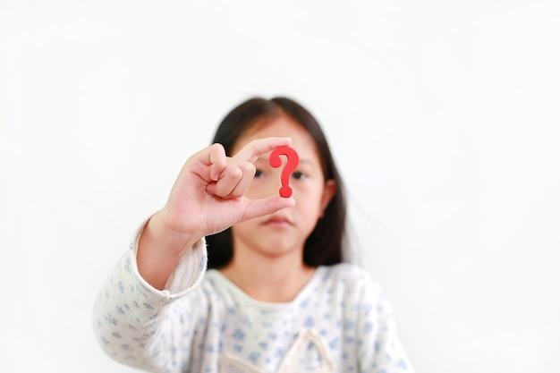 Menina criança asiática segurando o sinal de interrogação vermelho sobre fundo branco. foco seletivo