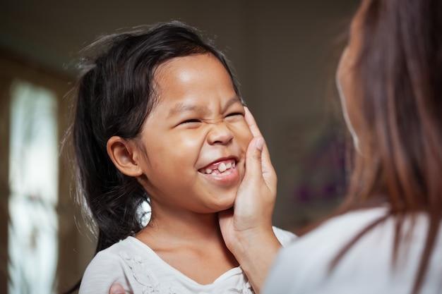 Menina criança asiática sorrindo quando a mãe tocando seu rosto