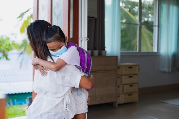 Menina criança asiática usando máscara médica para proteção situação de surto do vírus covid-19 abraçando sua mãe antes de sair como novo estilo de vida normal. conceito de saúde e distância social.