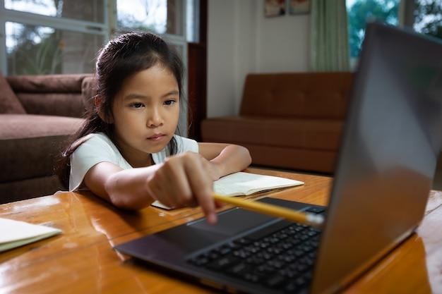 Menina criança asiática usando notebook para aprender tecnologia online em casa. conceito de educação online, ensino à distância social em casa durante a quarentena e as férias escolares.