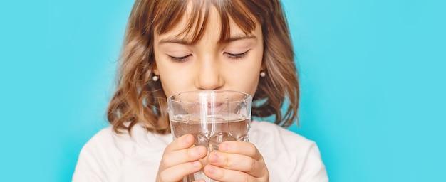 Menina criança bebe água de um copo. foco seletivo.