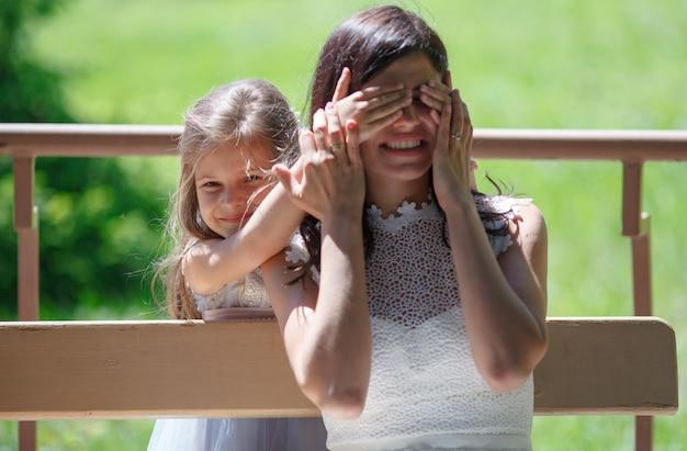 Menina criança brincando com a jovem mãe no parque ao ar livre.