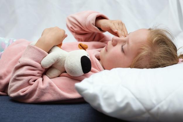 Menina criança chorando na cama, abraçando um brinquedo
