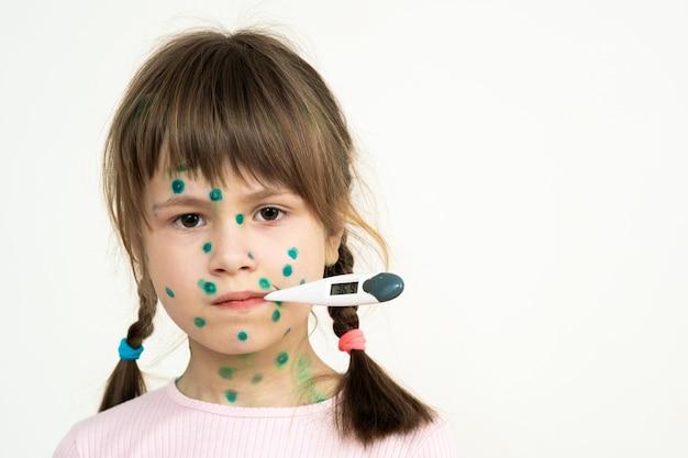 Menina criança coberta de erupções verdes no rosto doente com varicela, sarampo ou vírus da rubéola segurando um termômetro médico na boca