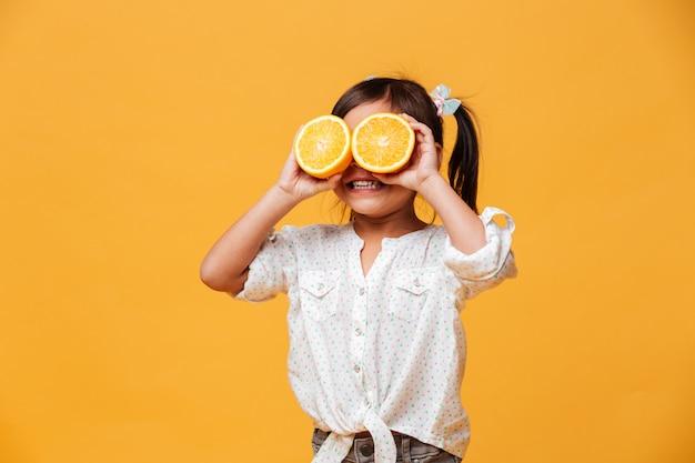 Menina criança cobrindo os olhos com laranja.