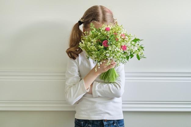 Menina criança com buquê de lindas flores da primavera