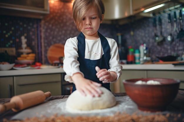 Menina criança com cabelo curto corte de cabelo cozinhar massa
