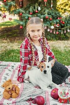 Menina criança com cachorro jack russell terrier perto da árvore de natal com presentes,