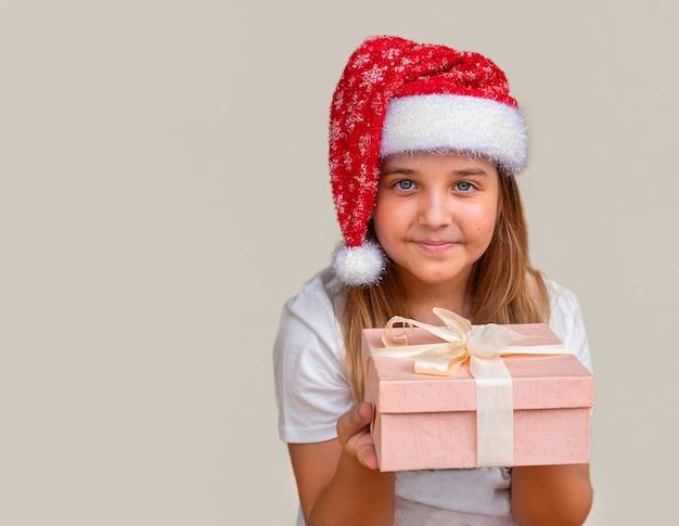 Menina criança com chapéu de papai noel segurando a caixa com o presente de natal