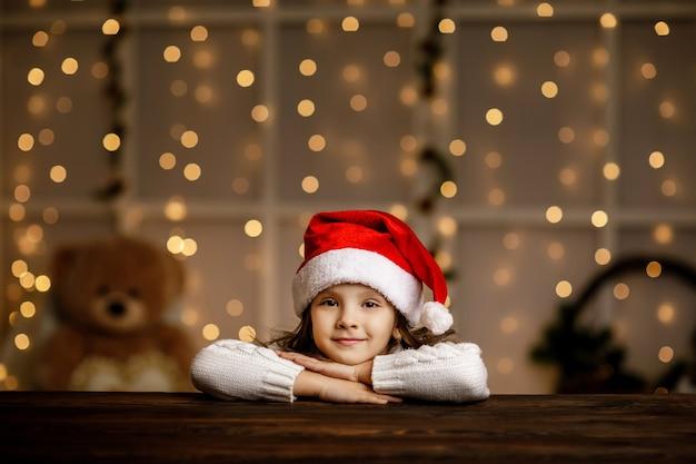 Menina criança com chapéu de papai noel sonhando com as férias