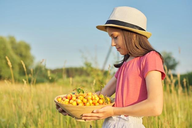 Menina criança com chapéu e tigela de frutas doces amarelas