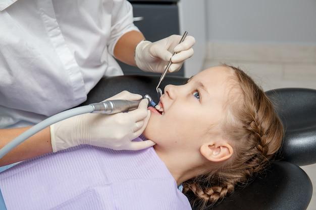 Menina criança com limpeza dentária profissional no consultório do dentista