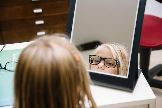 Menina criança com óculos, olhando no espelho