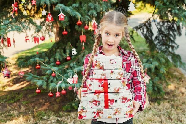 Menina criança com presentes perto de uma árvore de natal,