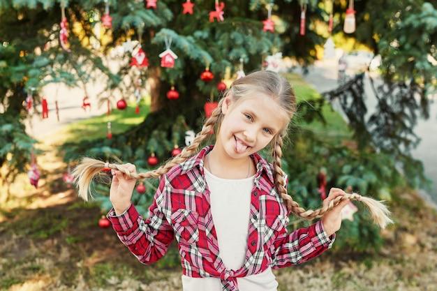 Menina criança com tranças no ensaio fotográfico de natal em julho no fundo de uma árvore de natal com presentes
