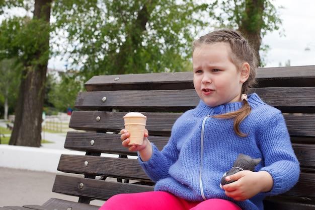 Menina criança com um suéter de malha azul come sorvete sentado em um banco.