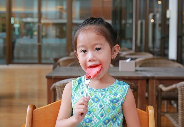Menina criança comendo fatia de melancia no restaurante com olhando para a câmera