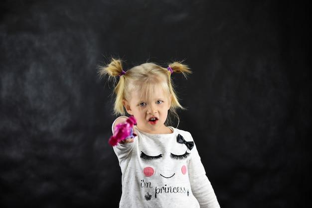 Menina criança conjura uma varinha mágica sobre um fundo preto