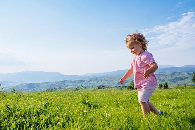 Menina criança correndo em um belo campo
