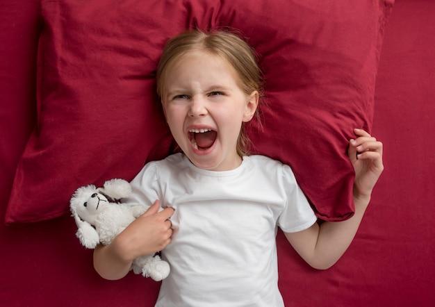 Menina criança deitada na cama se recusa a dormir