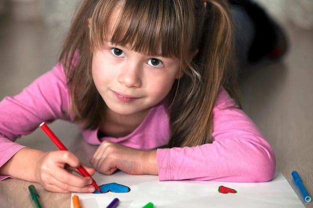 Menina criança desenhando com lápis coloridos em papel branco