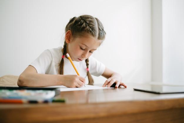Menina criança desenhando e pintando em casa enquanto está sentada à mesa