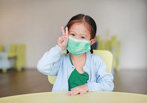 Menina criança, desgastar, um, máscara protetora, com, mostrando, dois dedos