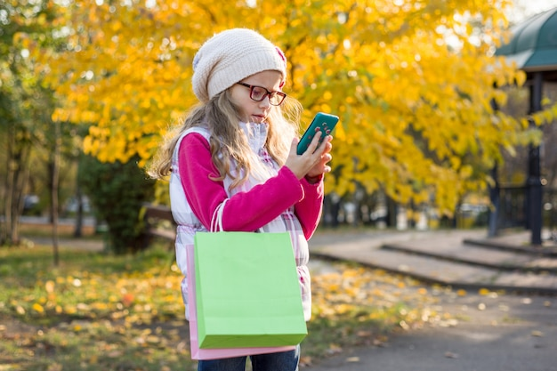 Menina criança e compras de outono