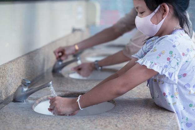 Menina criança e mãe lavar as mãos com usar máscara facial no banheiro