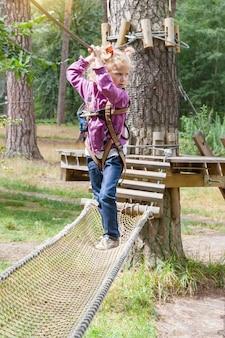 Menina criança, em, aventura, escalando, parque fio alto