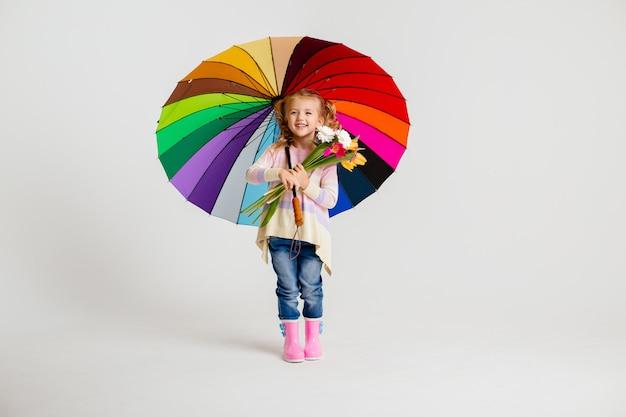 Menina criança em botas de borracha, segurando um guarda-chuva multicolorido