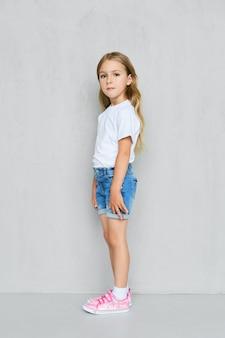 Menina criança em camiseta branca, shorts jeans e tênis rosa em pé de perfil perto da parede