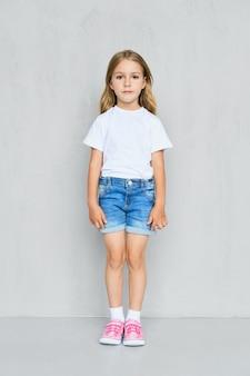 Menina criança em camiseta branca, shorts jeans e tênis rosa em pé perto da parede