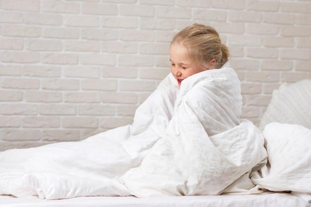 Menina criança, em, cobertor, sentar-se cama