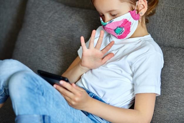 Menina criança em máscara em casa conversa vídeo com reunião tablet, amigo de chamada on-line
